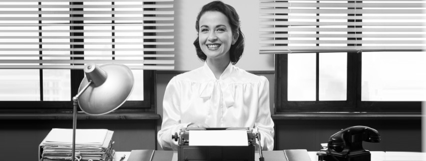 Smiling woman with typewriter and rotary phone
